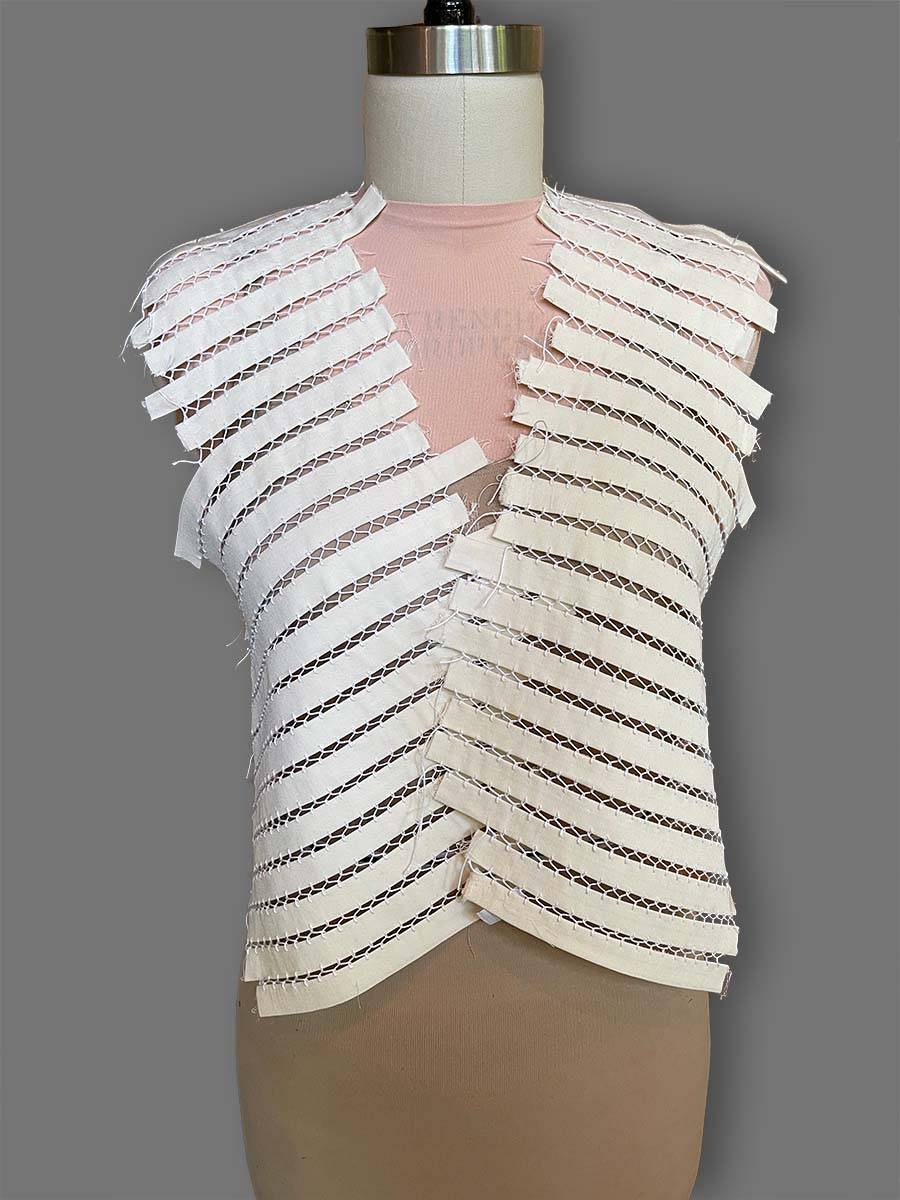 fabric strips lying on dress form and separated by fagoting stitches
