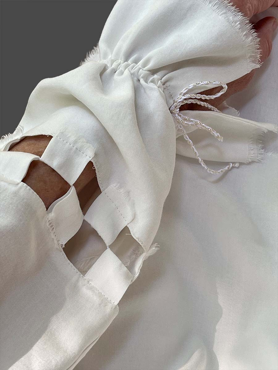 Checkerboard cut-out design on full sleeve of flowing tunic, which is gathered by white cord