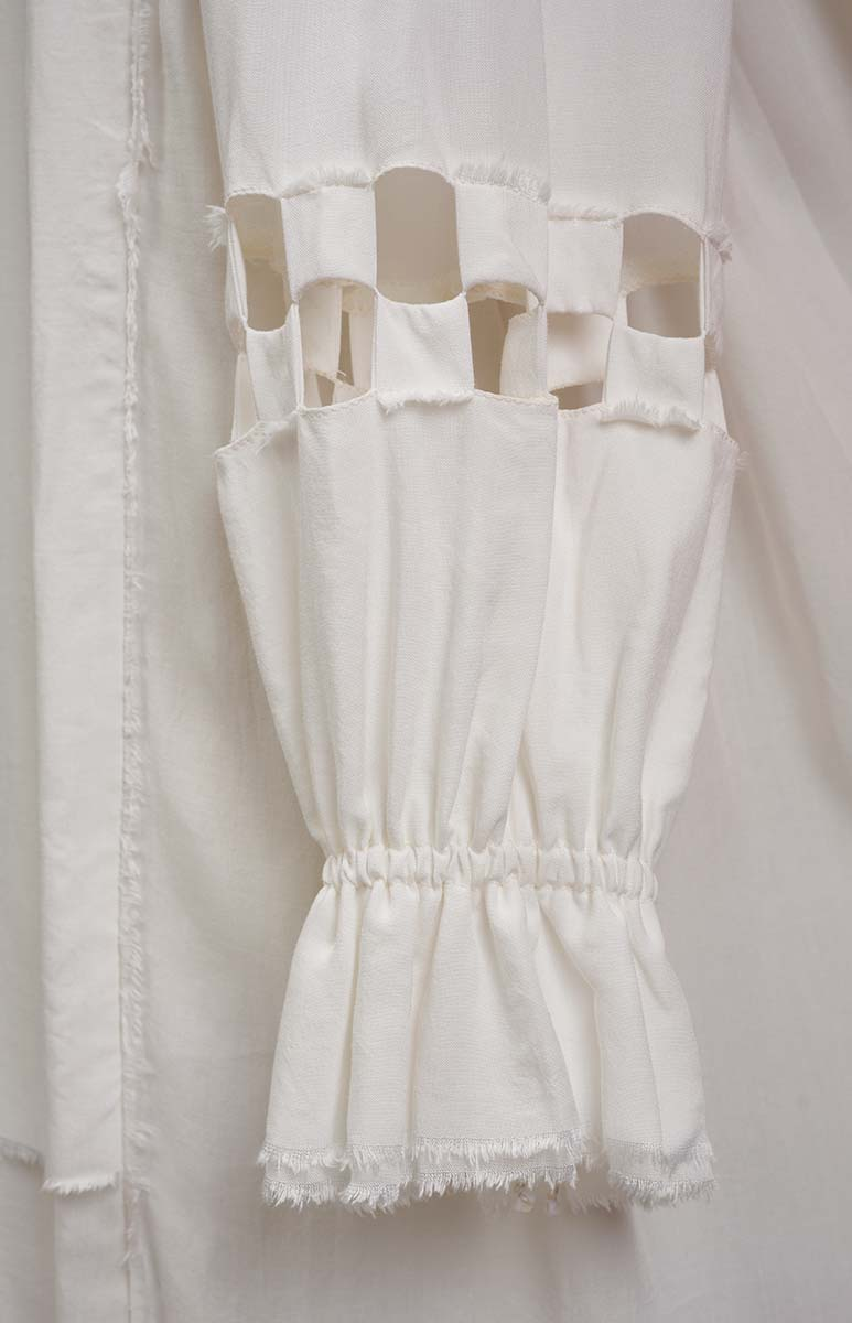 Checkerboard cut-out sleeve with gathered sleeve cuff on white flowing tunic