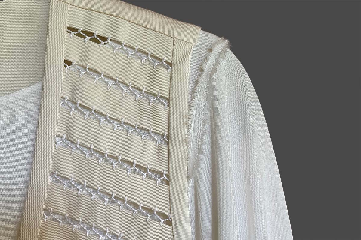 Close-up of shoulder of flowing tunic and tailored vest fagoting stitches