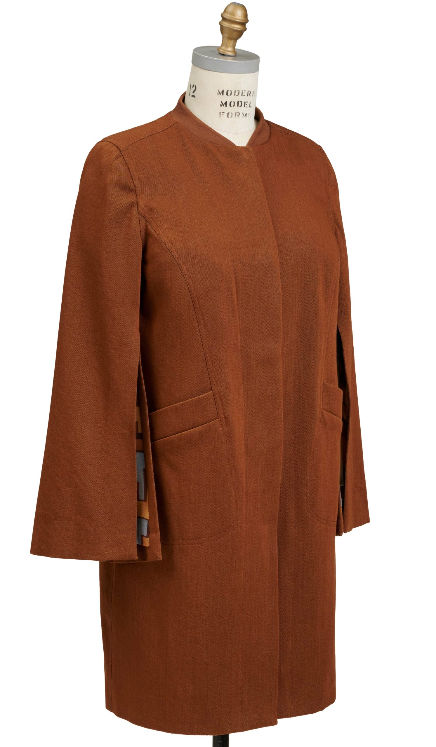 Brown coat on a dress form with hidden buttoning down the center front