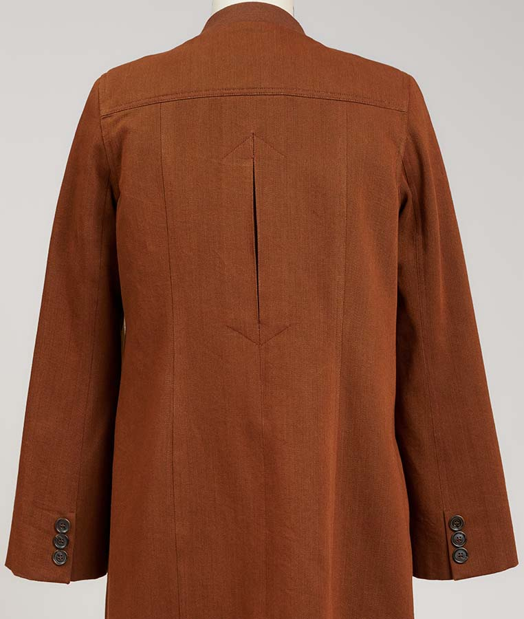 inverted closed pleat at the center back of a cape sleeve brown denim coat