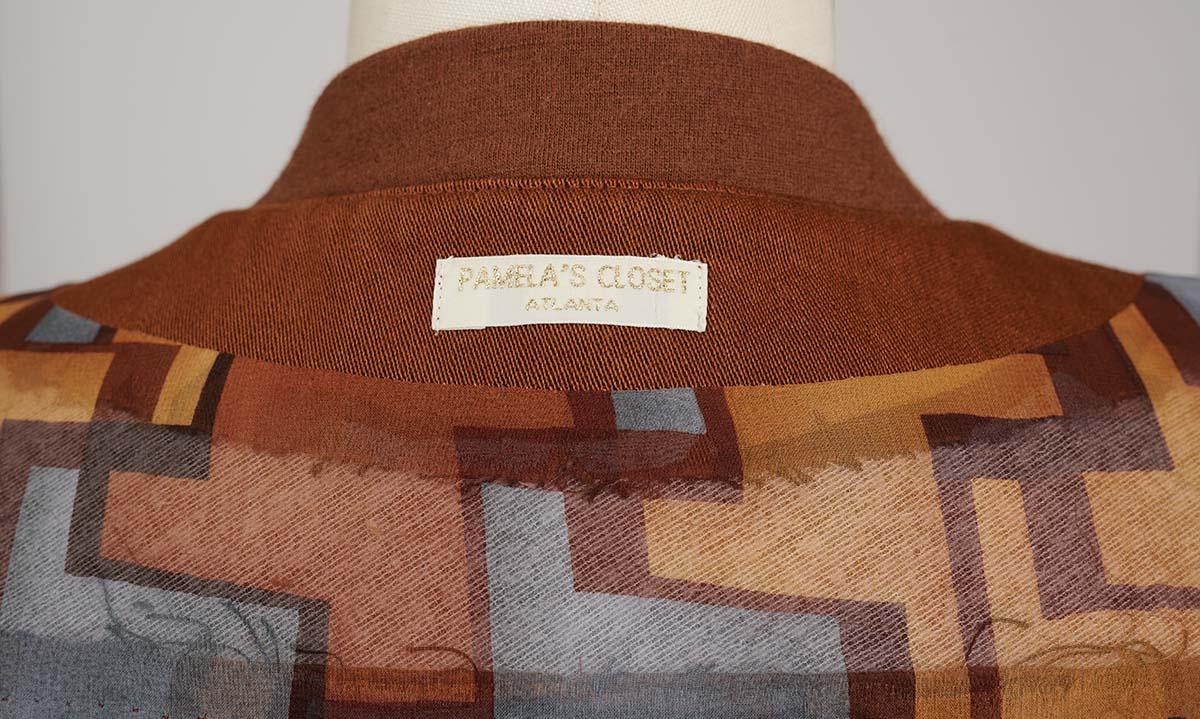Pamela's Closet label at the back neck of a cape sleeve coat