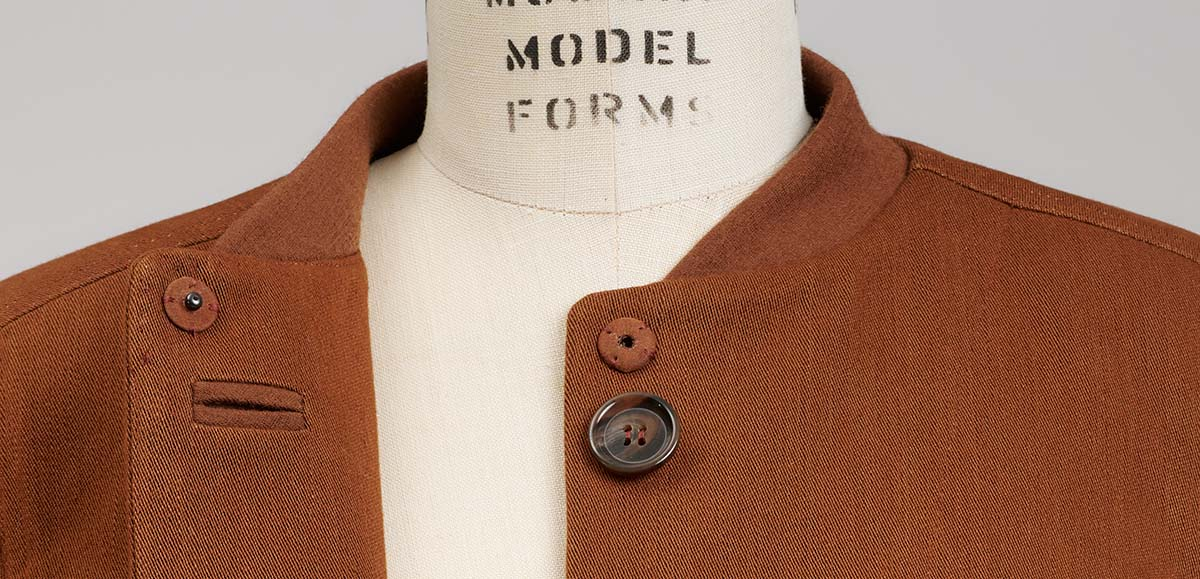 Close-up of brown denim coat's bomber-style collar and upper closure of covered snaps and hidden buttoning