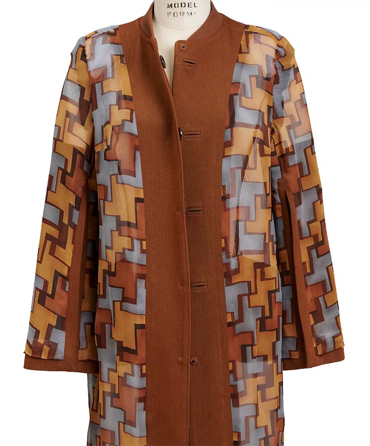 A cape sleeve coat with geometric print lining is draped inside out on a dress form