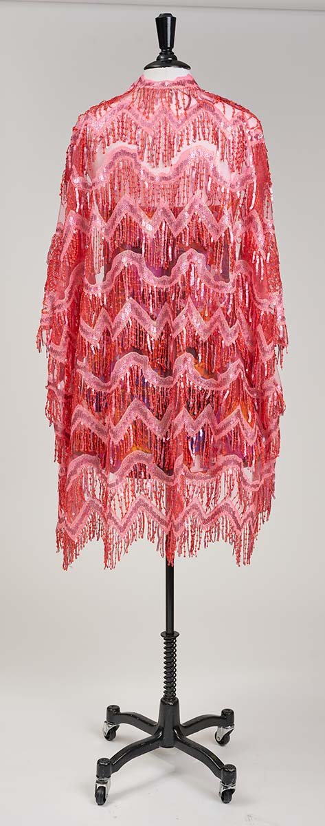 The back of a red and pink sequined and fringed jacket on a dress form