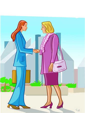 Two businesswomen shaking hands on a street