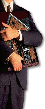 Man in a suit and tie clutching a house in his arms in a protective manner
