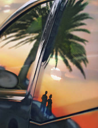Reflection of couple on beach at sunset in car window