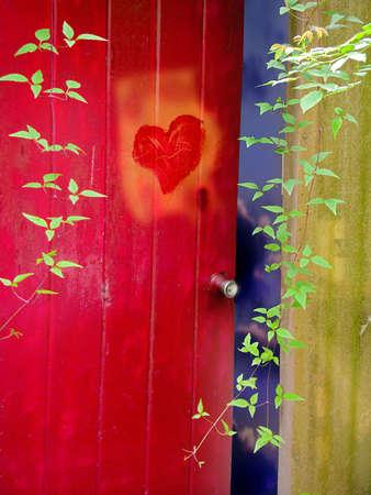 Heart on red door in garden