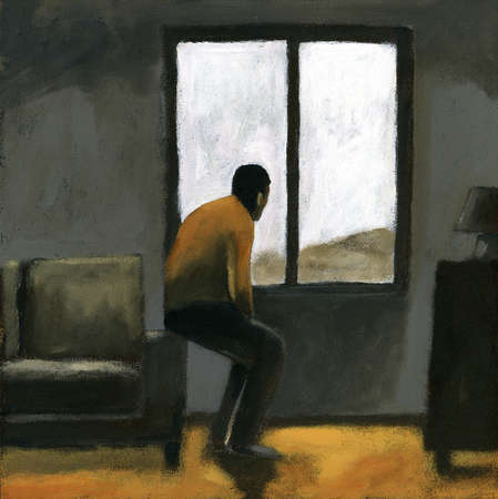 Man sitting on edge of sofa and looking out window