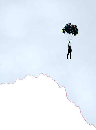 Man floating from helium balloons over cliff