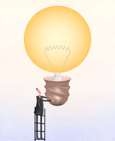 Man on ladder holding up lightbulb
