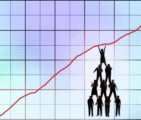 Group of business people trying to hold up a line chart