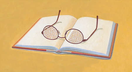 Open book with words showing through eyeglasses