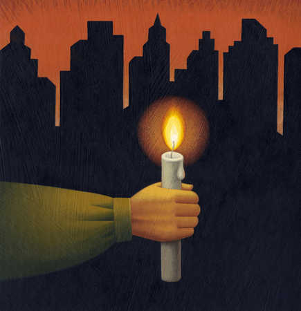 Hand holding candle in front of skyline