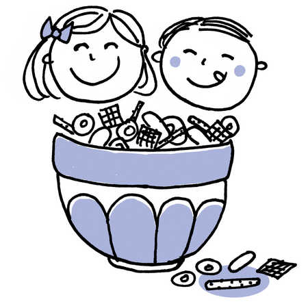 Boy and girl smiling next to bowl of candy