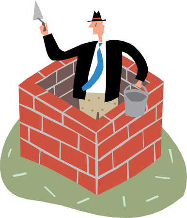 A man building a layer of bricks around himself