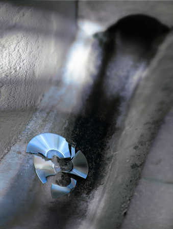 Broken and discarded compact disk in drain, close-up, high angle view