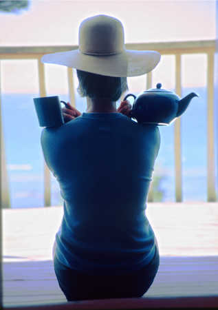 Woman holding tea cup and teapot on shoulders, rear view