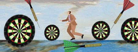 Businessman dodging darts and dartboards