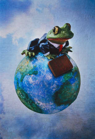 Frog wearing suit, lying on globe with briefcase