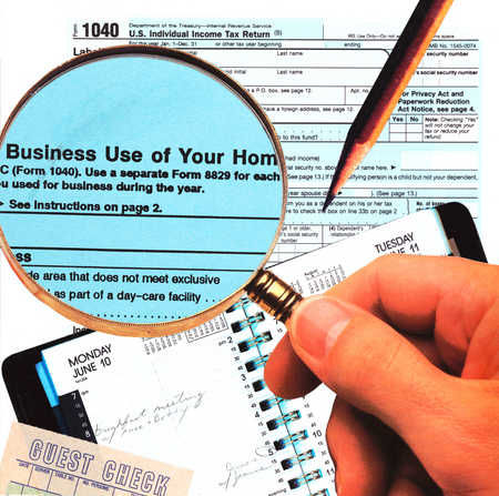 Hand Holding Magnifying Glass Over Tax Forms, Receipts