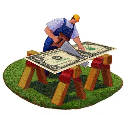 Construction worker sawing dollar bill in half