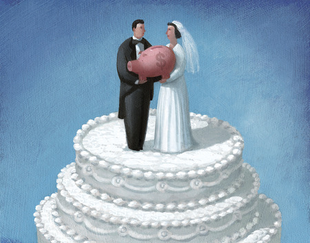 Bride and groom wedding cake toppers holding piggy bank
