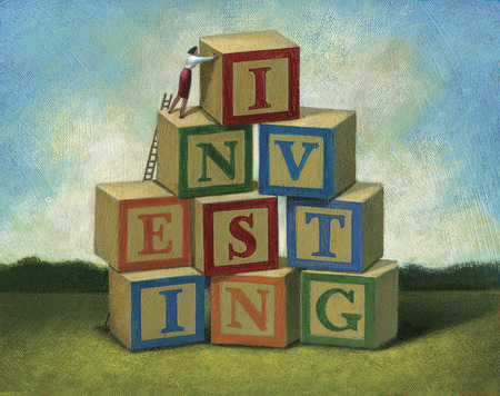 Businesswoman forming word 'Investing' with alphabet blocks