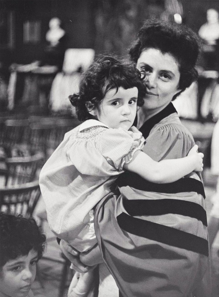 Alma Arbos, who received her Ph.D from Radcliffe in 1962, holds with her daughter during the Radcliffe Commencement ceremony. Radcliffe President Mary I. Bunting-Smith encouraged mothers to complete their degrees.
