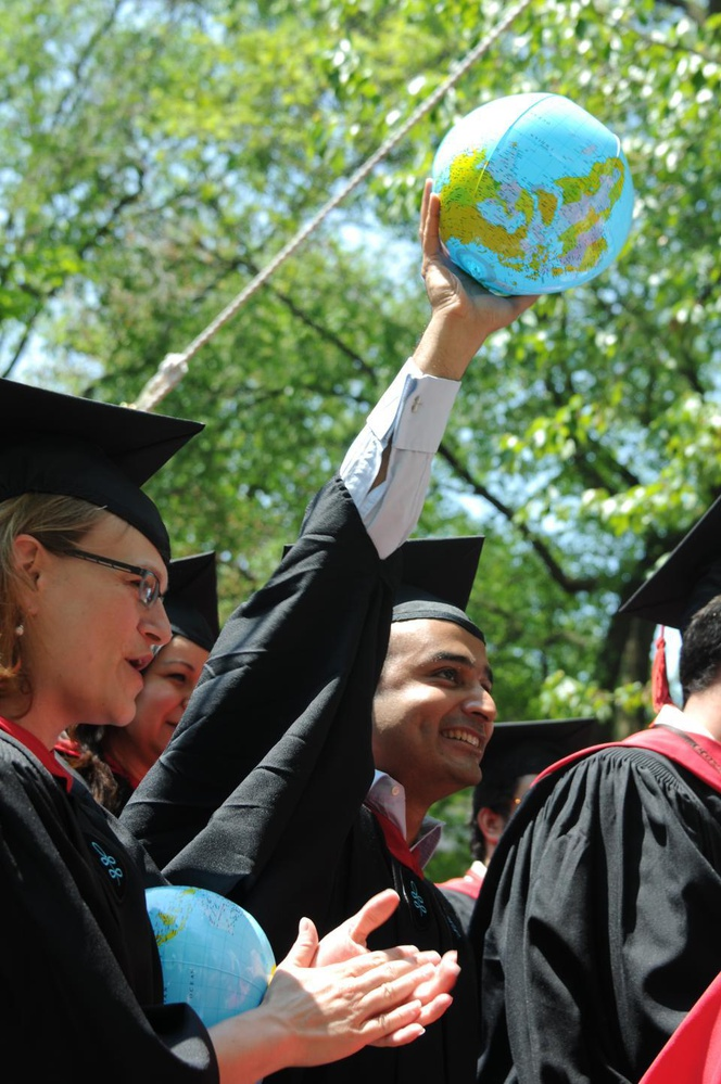Malik Ahmad Jalal holds up an inflatable globe and  cheers with his fellow students as they become Kennedy School of Government graduates during Commencement.