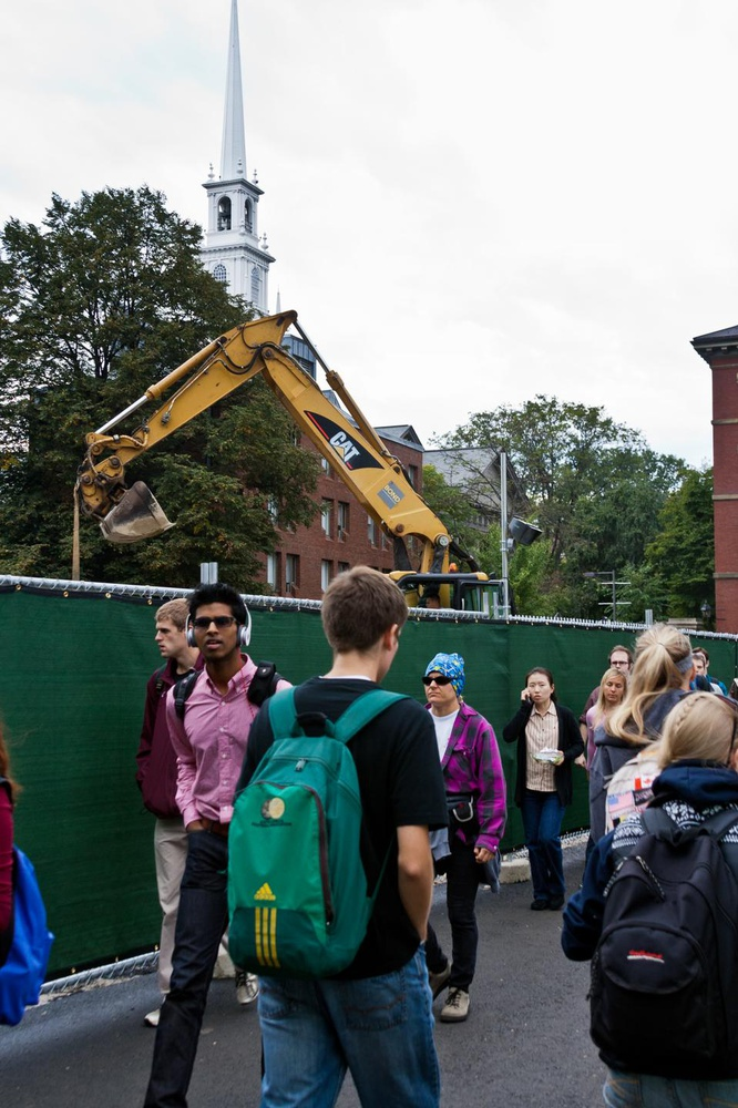 Students walk through the narrow passage in front of the Science Center as the construction work goes on. Harvard is transforming the plaza outside the Science Center as a part of the Common Spaces initiative.