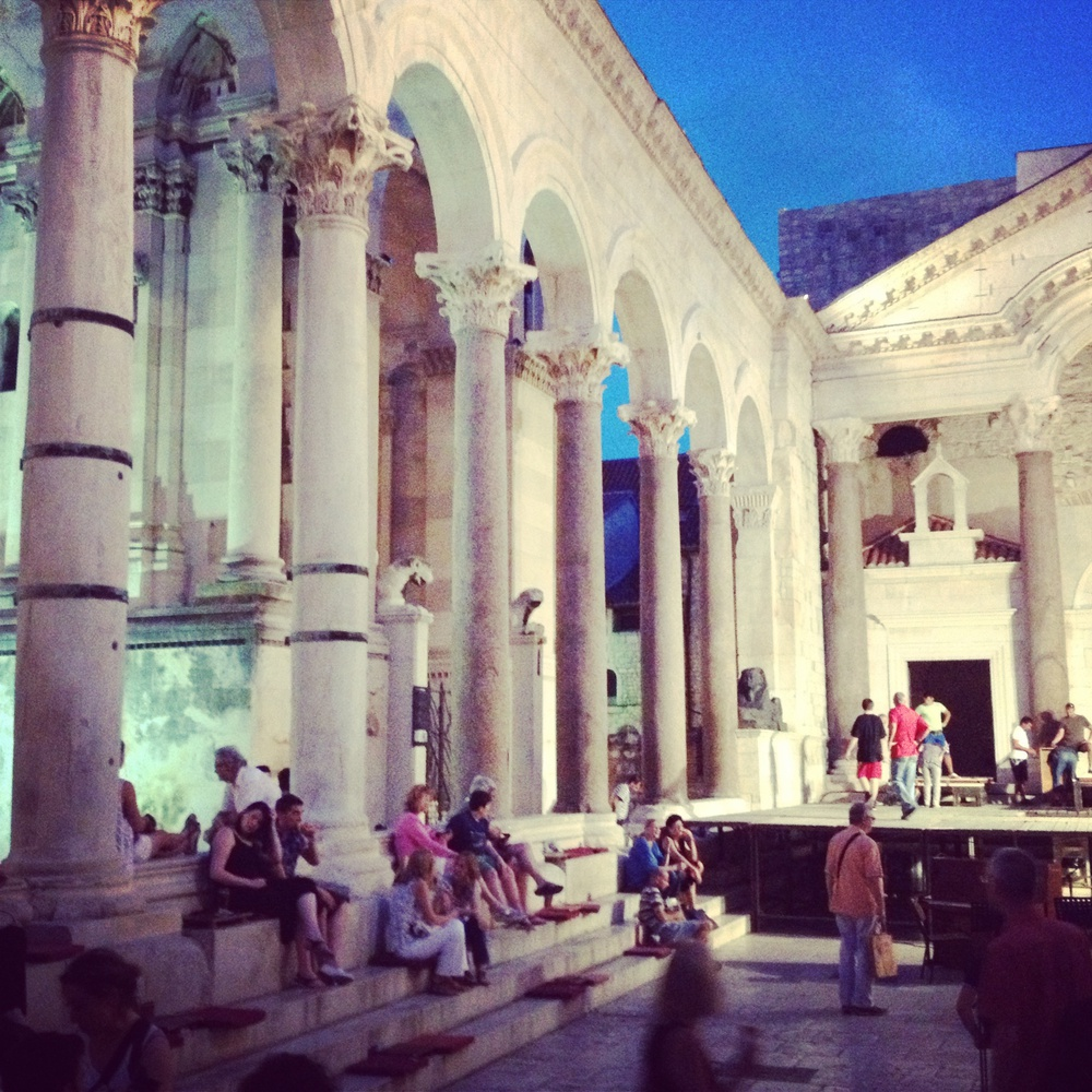 Tourists and locals sit on the steps of a courtyard in the ancient palace of Diocletian, a Roman emperor who built the palace in Split for his retirement.
