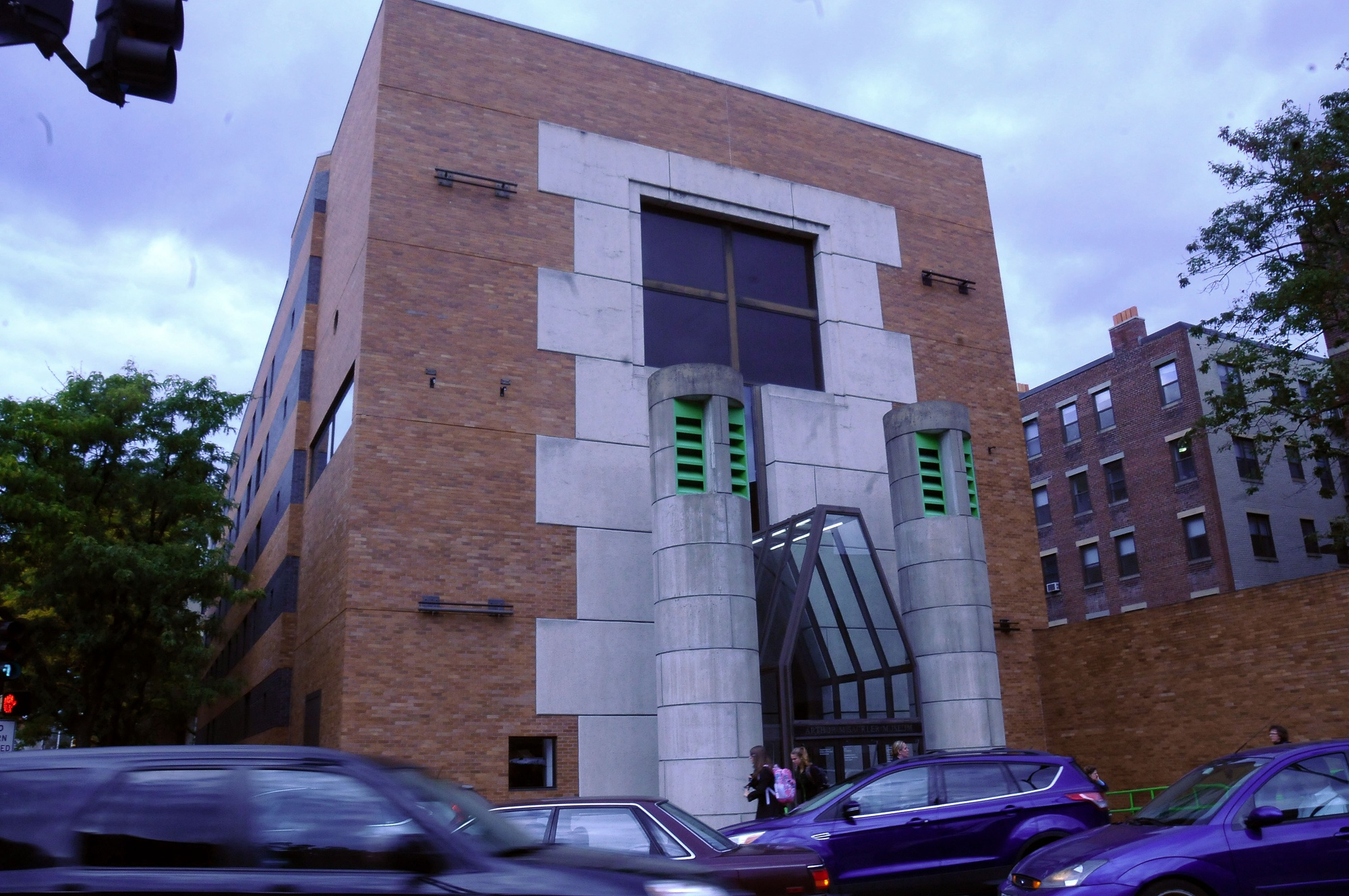 Cars drive past the busy geometric entrance of the Arthur M. Sackler Museum on Wednesday afternoon.