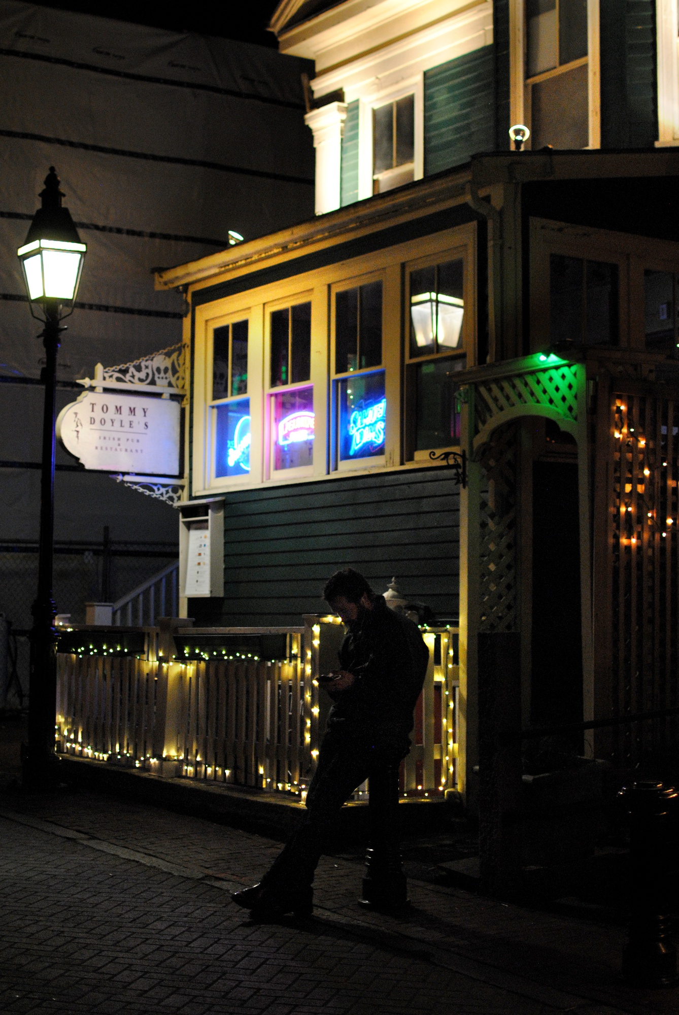A man stands outside Harvard Square's classic pub, Tommy Doyle's, on Sunday night. The central location of Tommy Doyle's to Harvard's campus has made it a popular spot for students, but the business will close by the end of December.