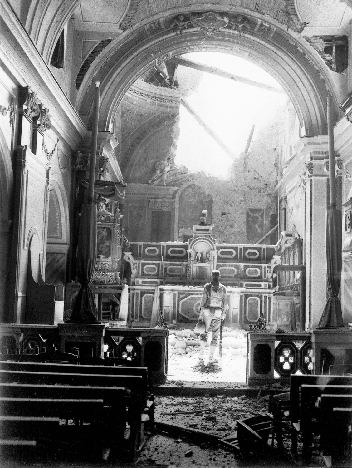 A private enters a bombed-out cathedral in Acerno, Italy, during WWII.