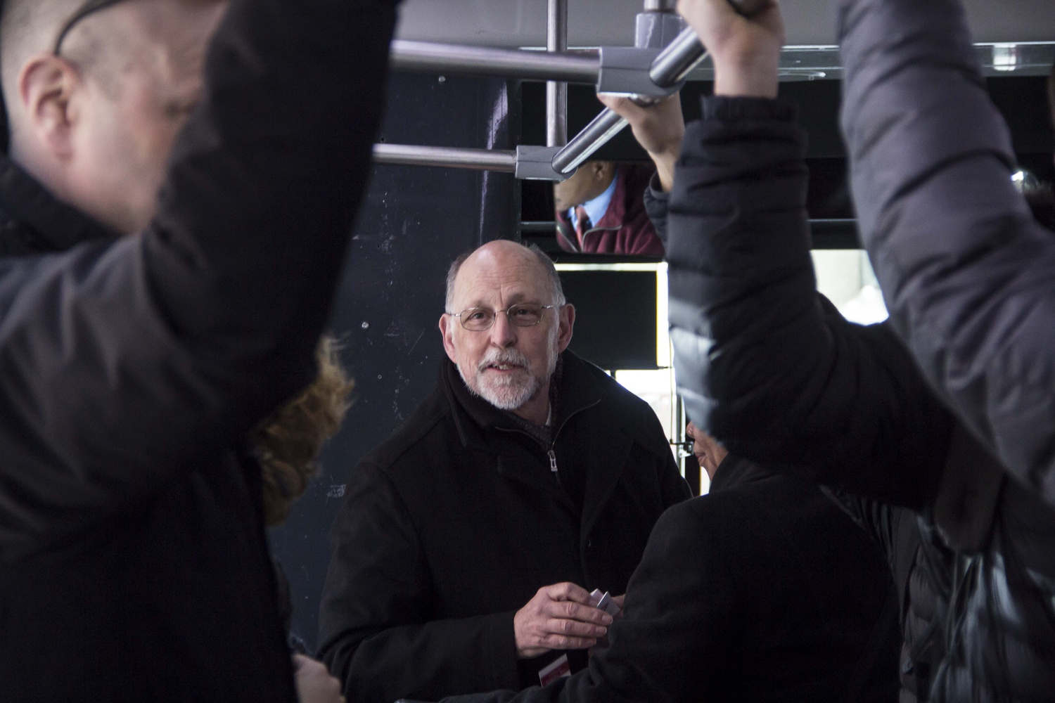 Dean Pfister hands out bookmarks to students on an early-morning shuttle ride on the Mather Express route. He gave hints indicating his shuttle ride in an email send out the day before.