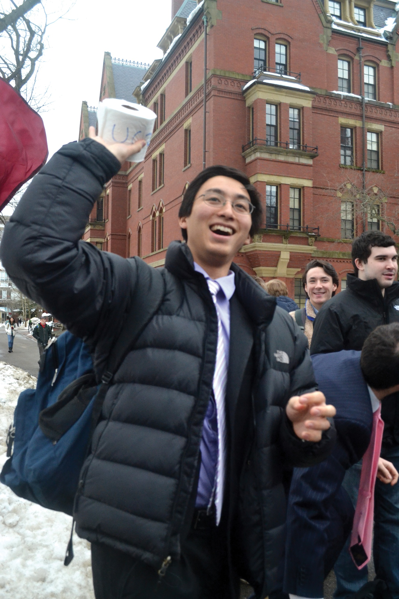 Undergraduate Council Vice President Sietse K. Goffard '15 throws toilet paper to a crowd of students during an organized rally to ask the university for increased funding.