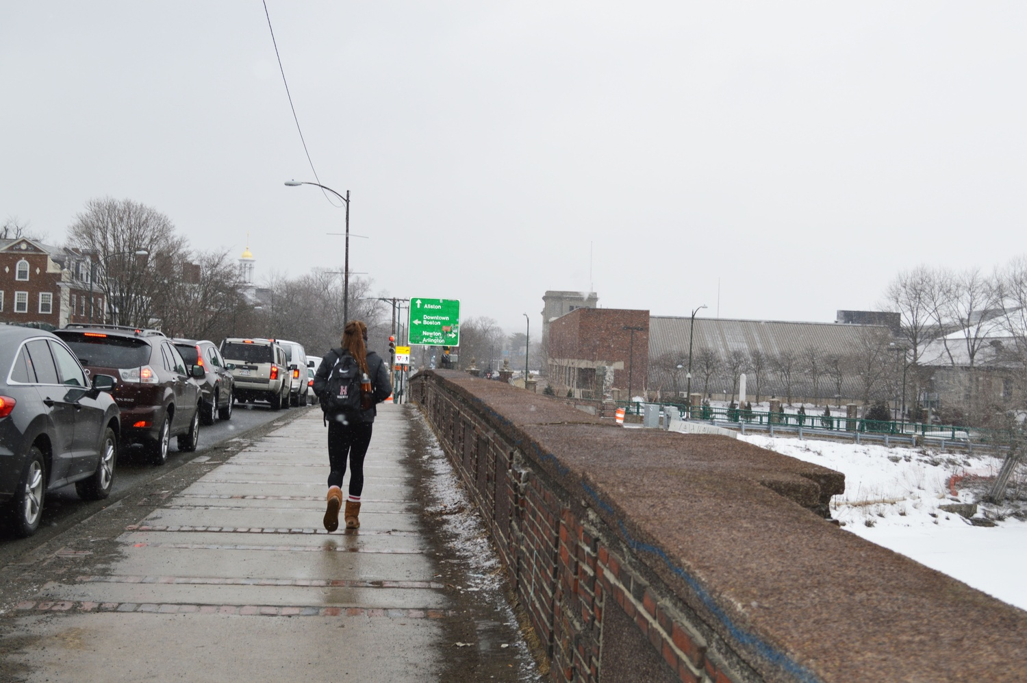 A member of the women's hockey team jogs across Anderson Bridge to get to practice.