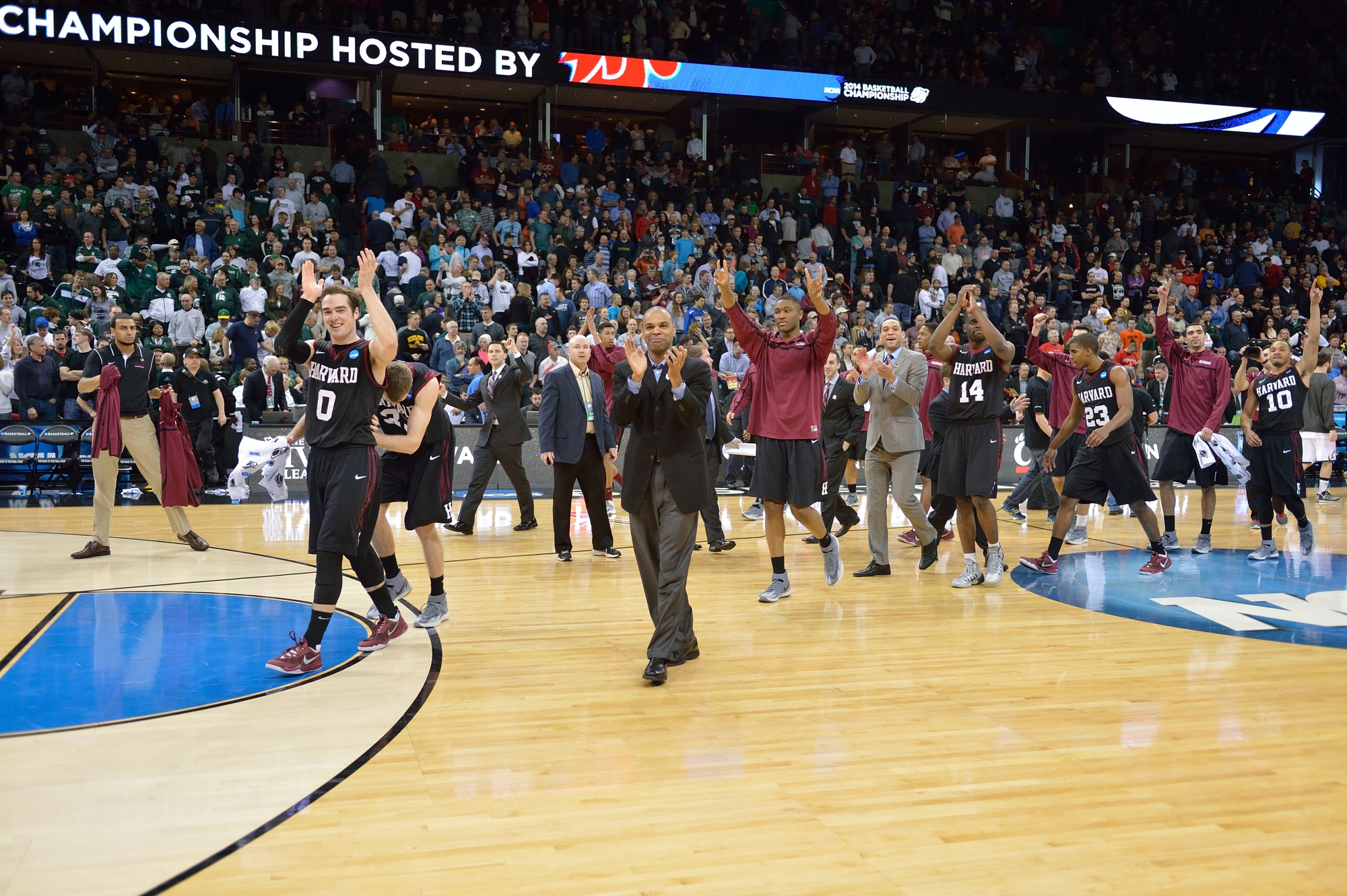 Harvard coach Tommy Amaker and his men's basketball team applaud the Crimson fan section after the squad upset Cincinnati, 61-57, in the second round of the NCAA Tournament.
