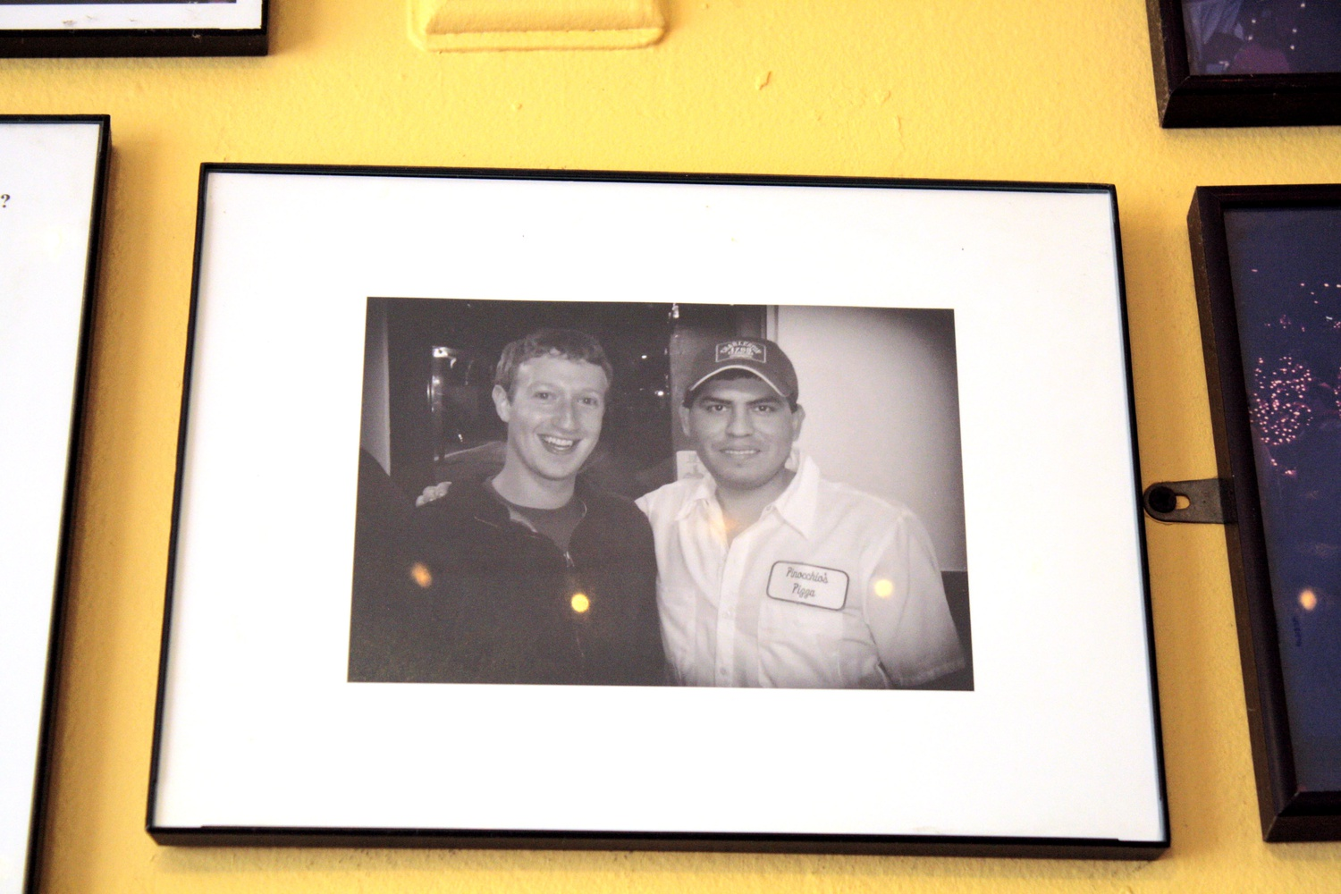 A picture of the Zucc lies on the wall of Noch's, gazing upon Harvard students as they gobble pizza