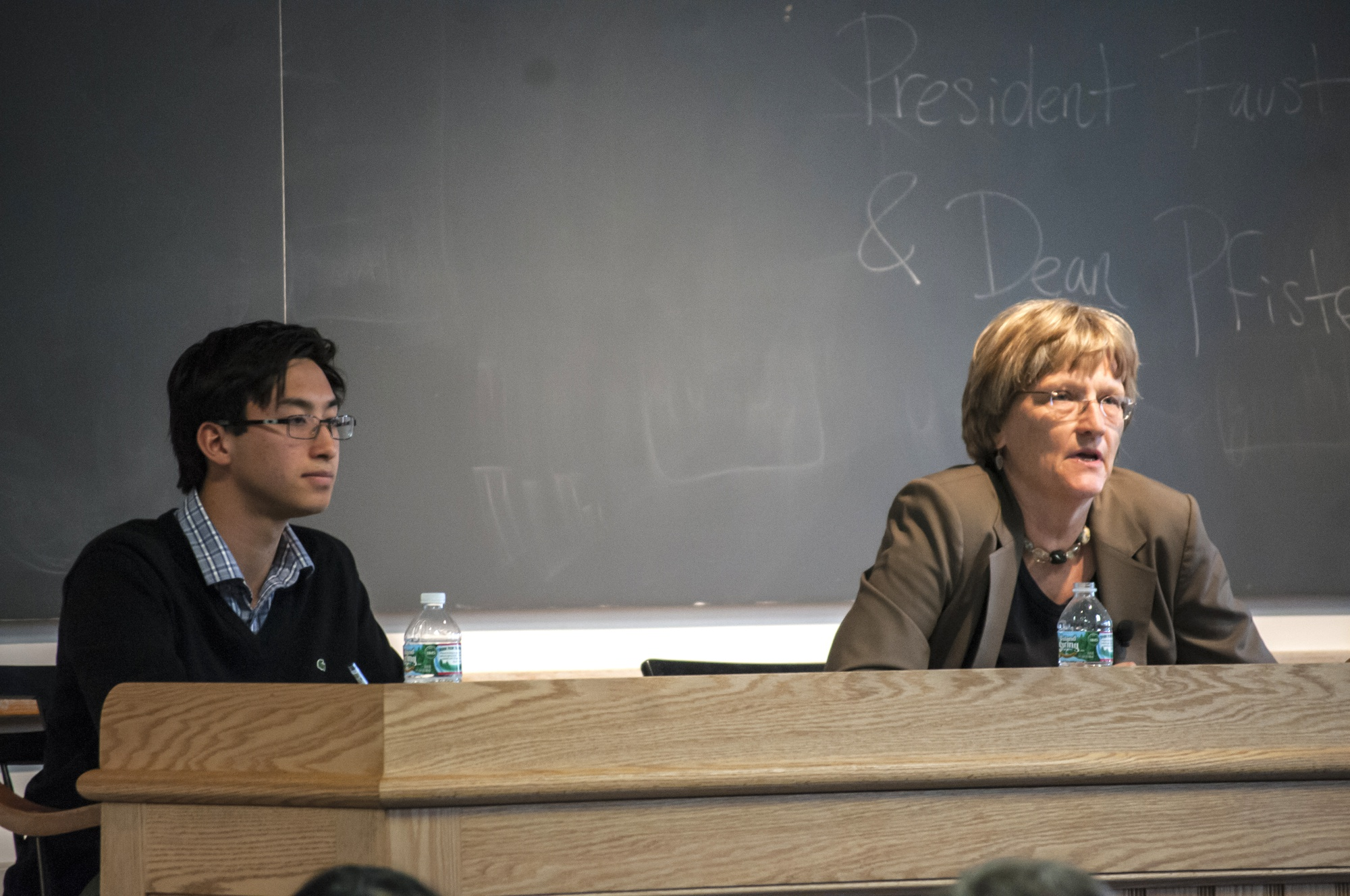 UC Vice President Sietse K. Goffard '15, left, listens to University President Drew G. Faust as she answers a question during an open meeting with the student body.