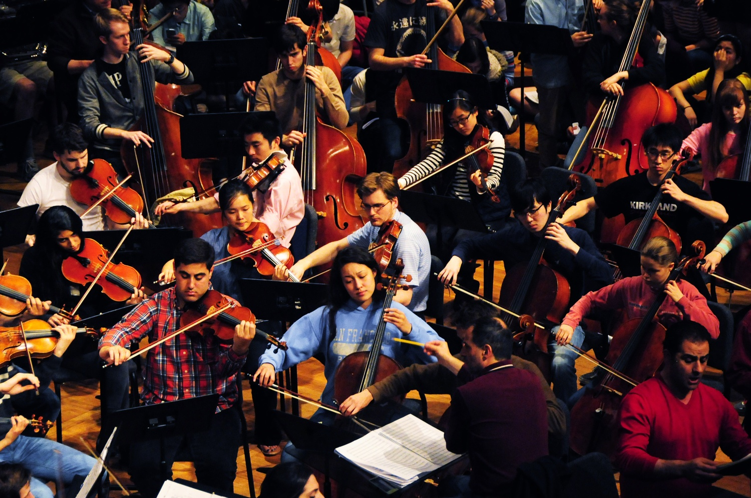 """Members of the Harvard-Radcliffe Orchestra gather in Sanders in April for rehearsal in preparation for """"Verdi's Requiem."""""""
