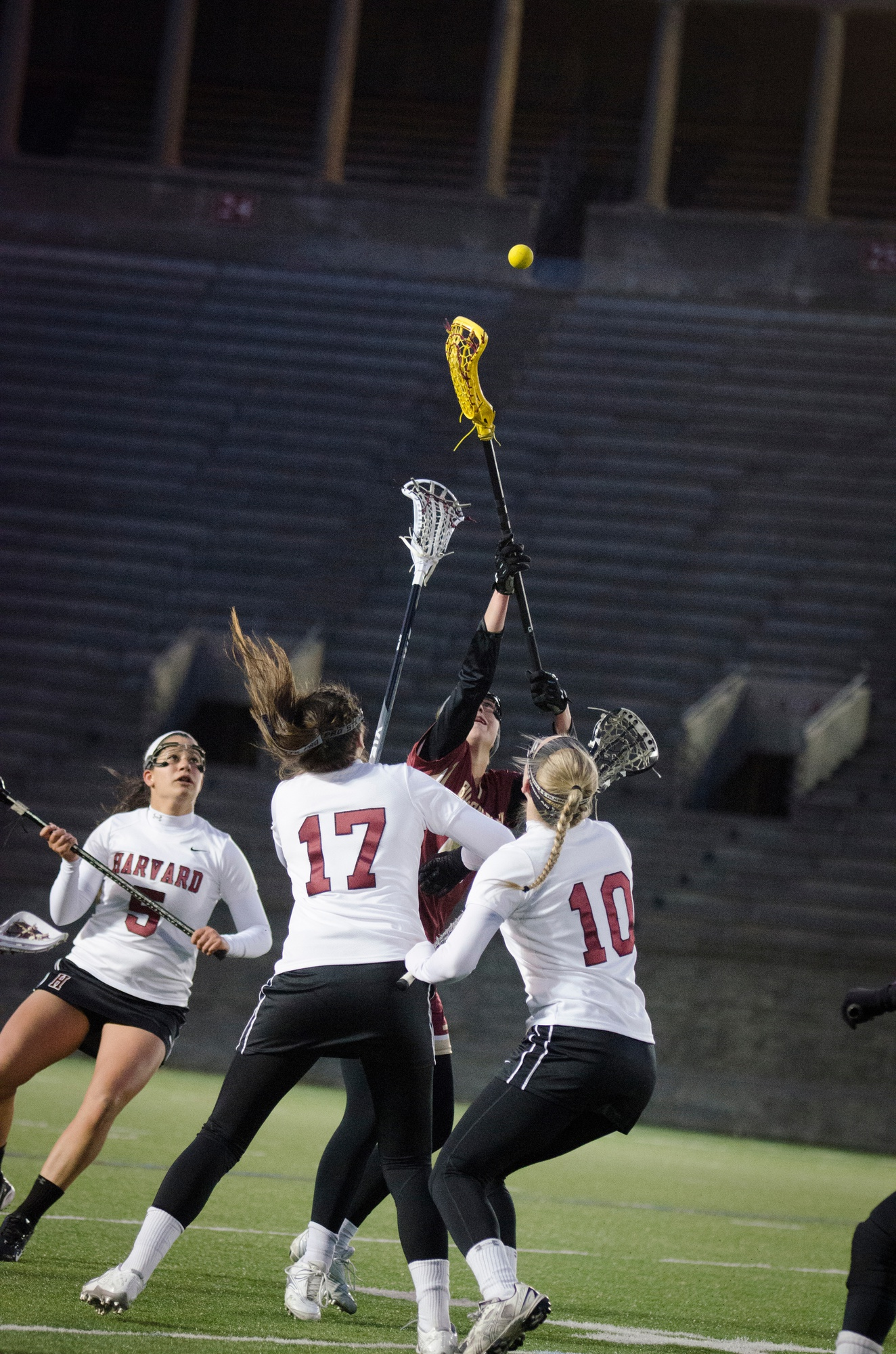 Sophomore defender Tory Waldstein, freshman defender Marina Burke, and sophomore defender Mia Capone battle for the ball in a contest against crosstown rival Boston University. Harvard prevailed, 11-6.
