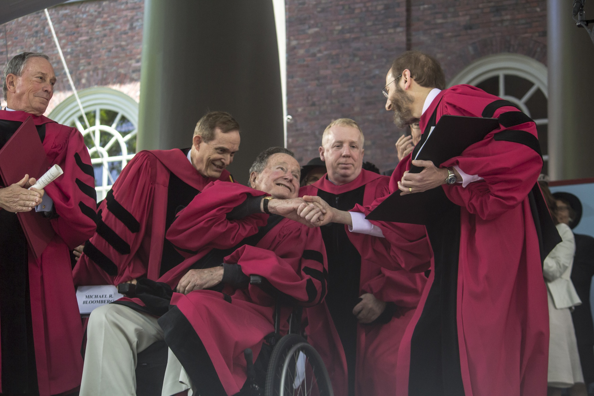 Former President George H. W. Bush shakes hands with University Provost Alan M. Garber, right, as he receives his honorary degree from Harvard University Thursday.