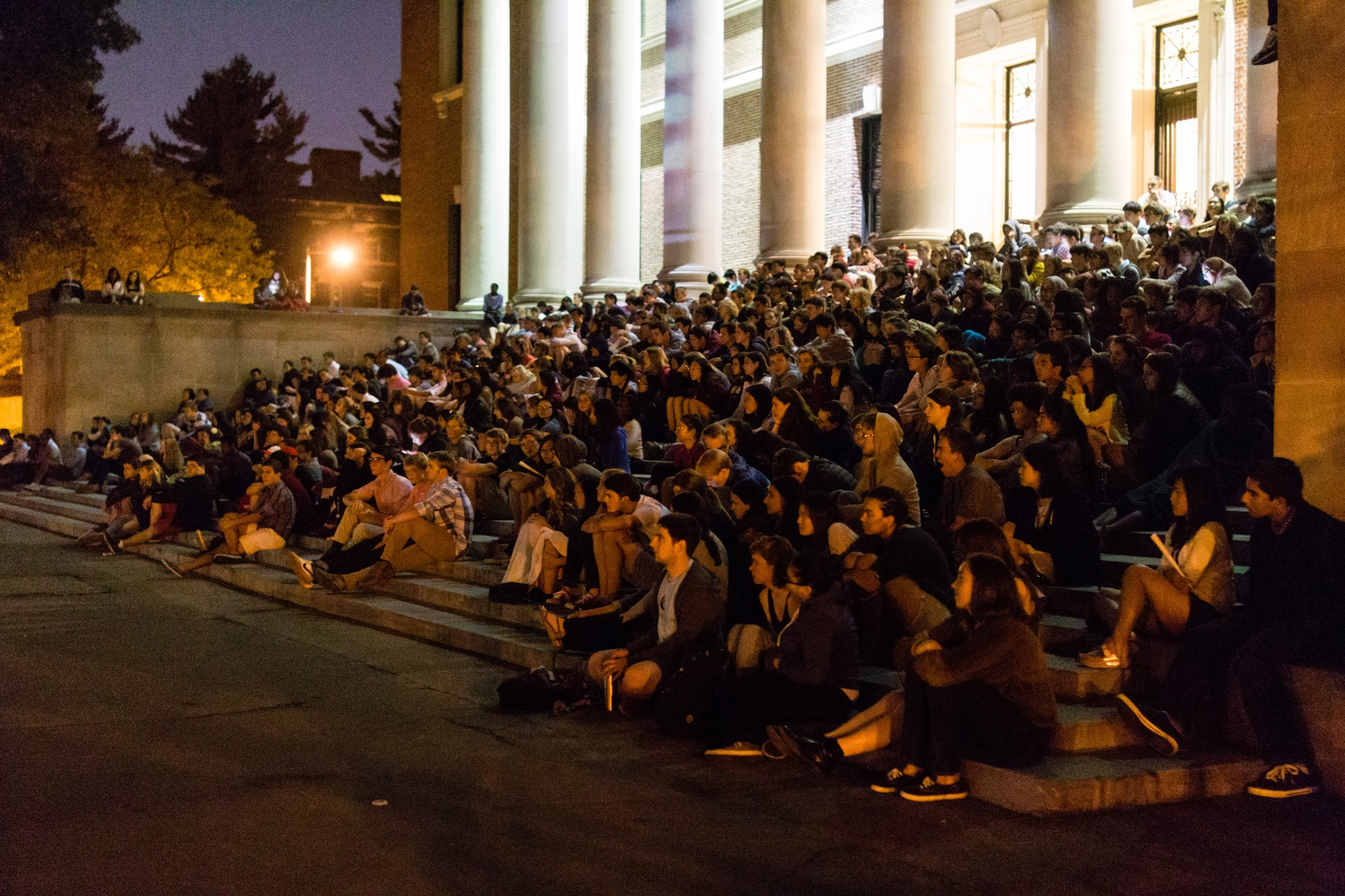 """Freshmen gather on the steps of Widener Library to watch the screening of """"Legally Blonde,"""" hosted by the College Events Board on Thursday, Aug. 29."""
