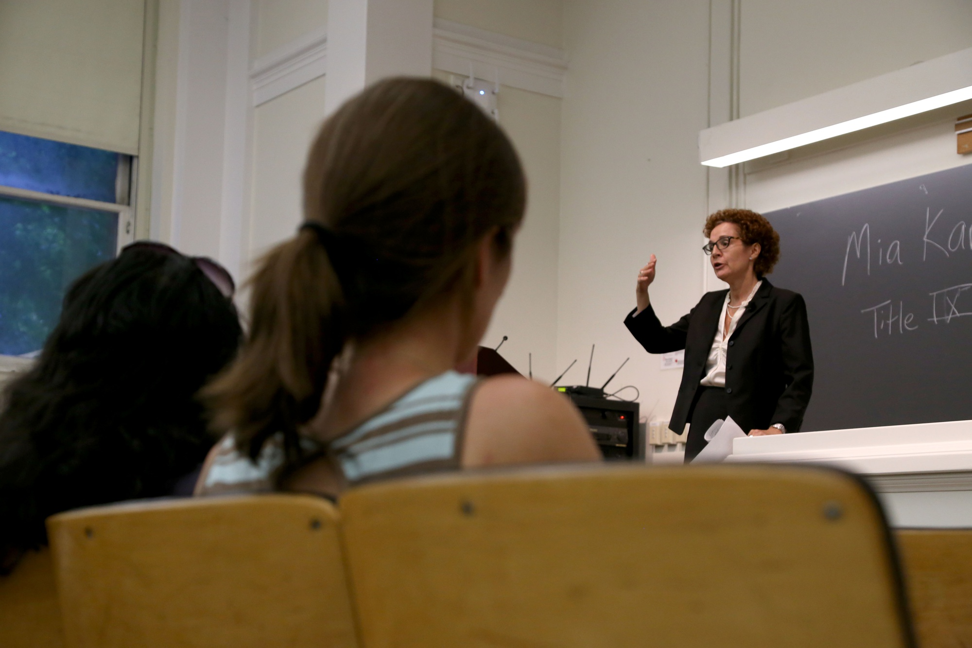 Members of the Harvard community watch as Mia Karvonides, Harvard's Title IX officer, speaks about the University's new sexual harassment policy and procedure in September. The community discussion, held in Emerson Hall, was the first in a series of meetings on sexual harassment policy open to the Harvard community.