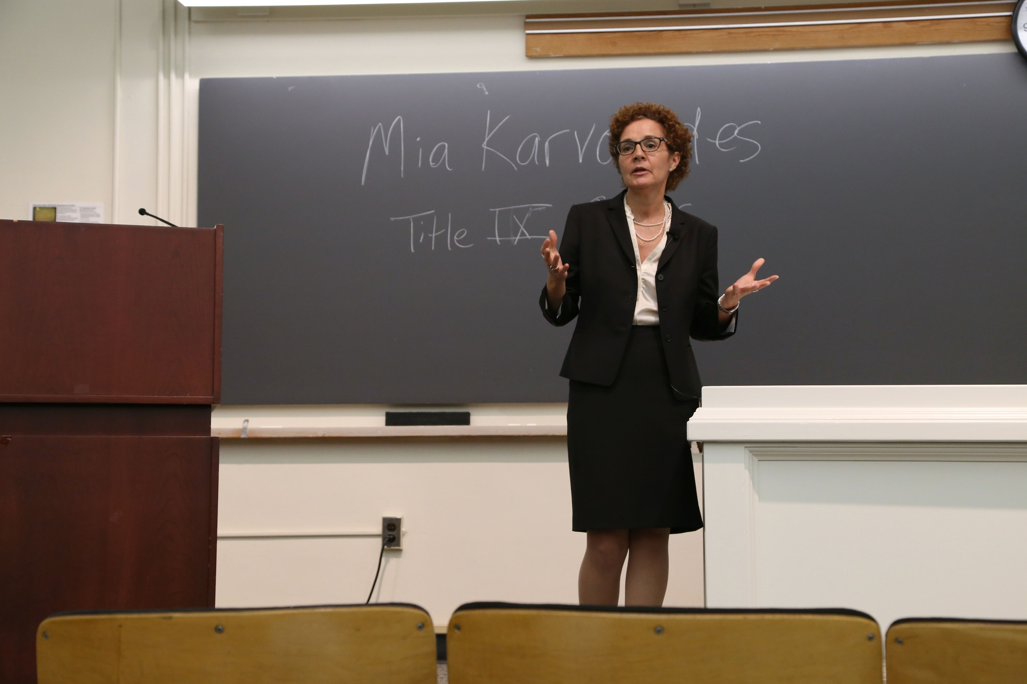 Members of the Harvard community watch as Mia Karvonides, Harvard's Title IX officer, speaks about Harvard's new sexual harassment policy and procedure on Tuesday evening. The community discussion, held in Emerson hall, was the first in a series of meetings on sexual harassment policy open to the Harvard community.