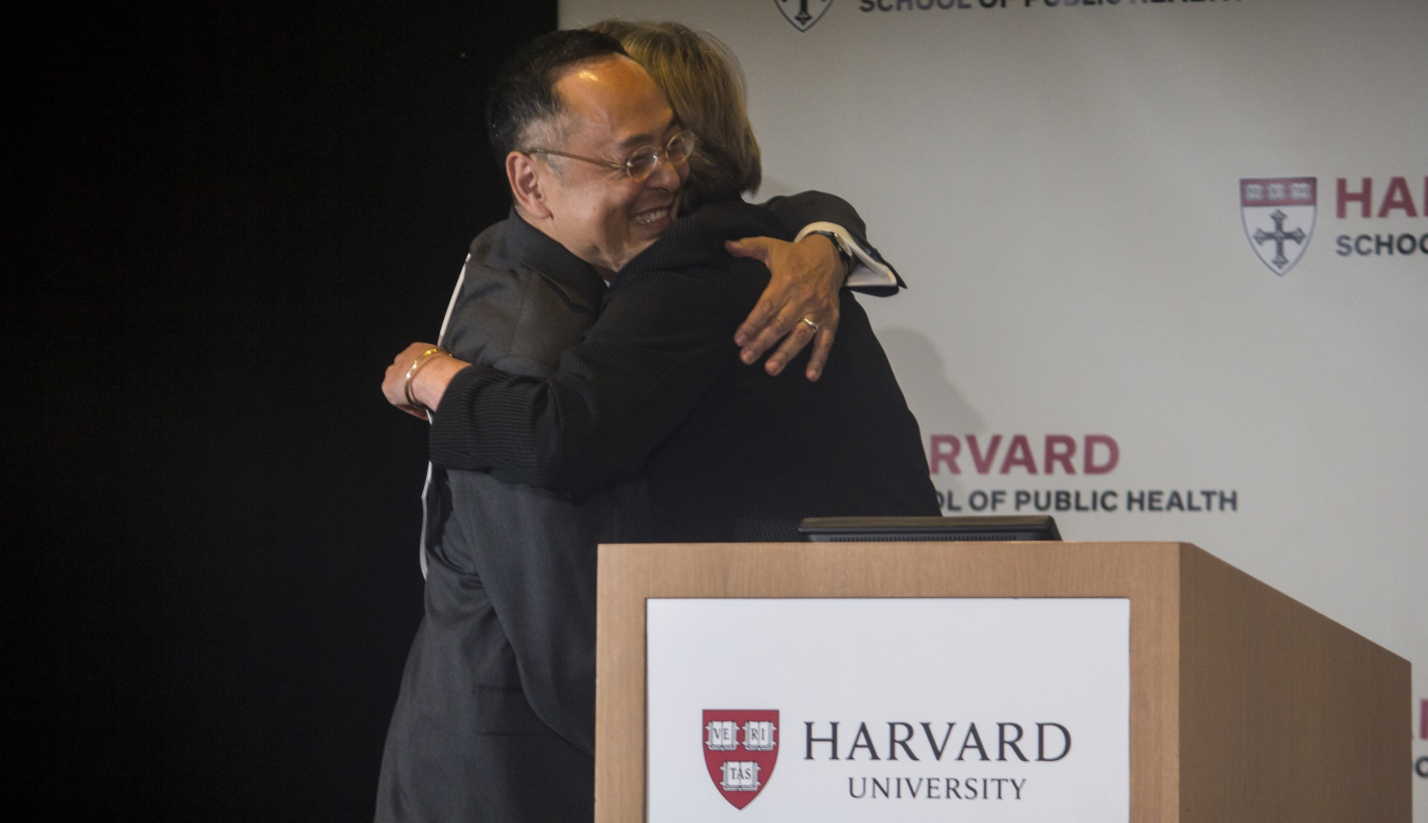 Gerald L. Chan, left, and University President Drew G. Faust embrace as Faust welcomes Chan on stage at the Harvard School of Public Health Monday afternoon for the unveiling of his foundation's $350 million gift.